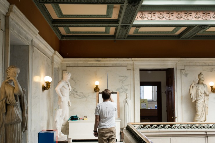 A student sketches marble statues in the Main Building.