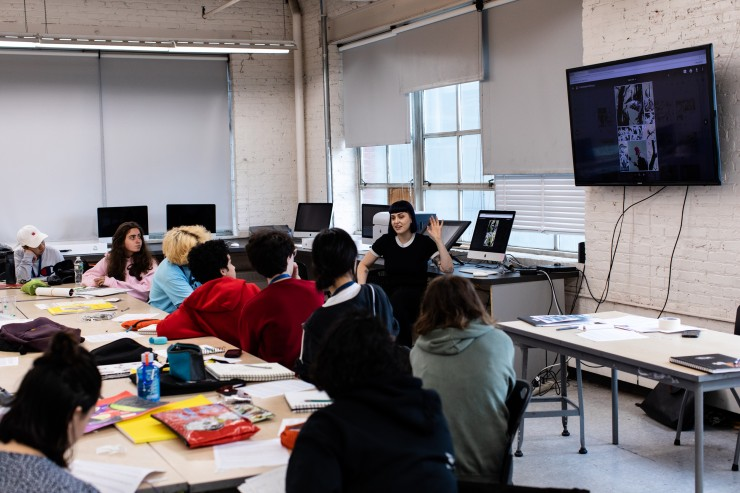 Students view artwork on a large screen. A faculty member sits at the front of the class.
