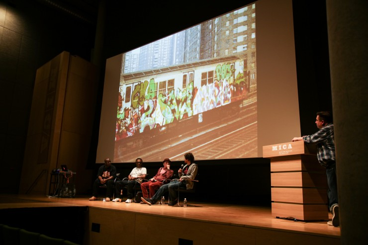 A panel of speakers sits on stage. Behind them is a projection of graffiti.