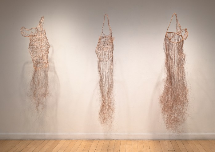 Copper wire silhouettes of evening dresses.