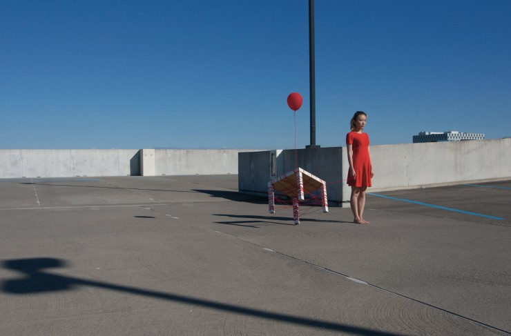 A woman in a red dress stands near a table wrapped in red yarn. The table is partially lifted off the ground by a single red balloon.