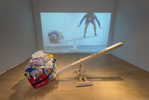 Seesaw in front of a video projection. A bundle of books, blankets and other miscellaneous items weigh down one side of the seesaw. The video projection shows the same seesaw, only with the artist attempting to balance on the side opposite of the bundle.