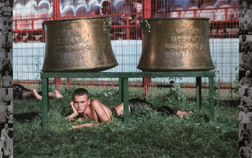 Photograph of a young man laying under a pair of giant metal bells.