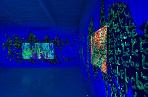 Two panels of script glow neon under black lights. The script continues off the canvas and on to the walls of the gallery.