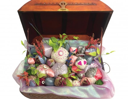 A wooden trunk filled with beaded soft sculptures.