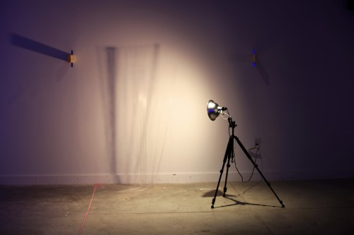 Installation of light and shadows. A lamp on a tripod throws shadows of string against the walls.