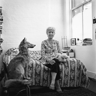 Joan Jonas seated on a bed with two dogs