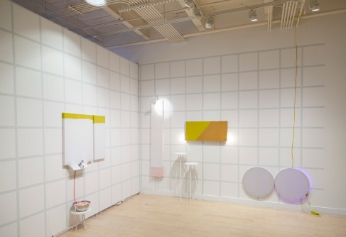 Minimalist/abstract bathroom furniture in a gallery space with a grid painted on the walls.