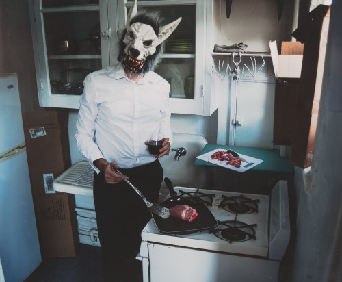 A man in a wolf mask stands in a kitchen cooking raw meat and drikning red wine.
