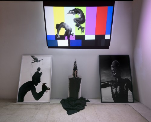Gallery space with video, two paintings, and a sculptural work. The video still is of a striped screen with a man jumping backwards into space.