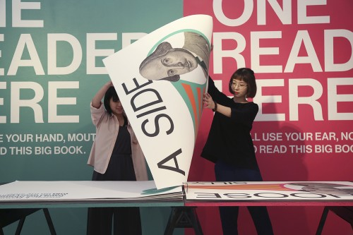 Oversized book with paged being turned by two individuals. The wall behind the book is painted with directions on how two people can read the book in tandem.