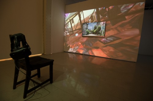 Projection of a VR simulation. A screen that shows what the viewer is seeing sits in the middle of the projection. A burnt chair stands in the middle of the gallery with a VR headset placed on it.