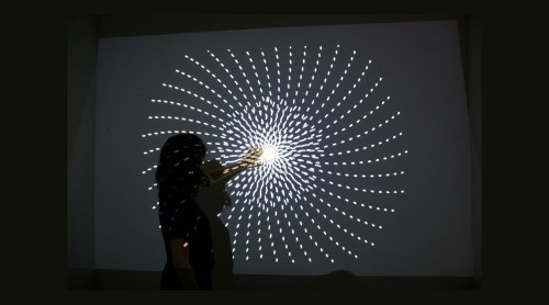 Projection of a large white spiral in a dark room. A student stands in front of the projection with her hand near the middle of spiral.