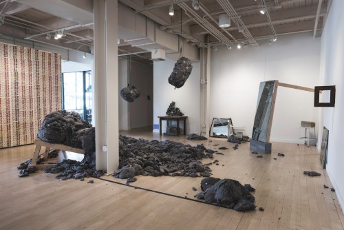 An enormous amount of fluffy gray lint is piled in the middle of a gallery space.