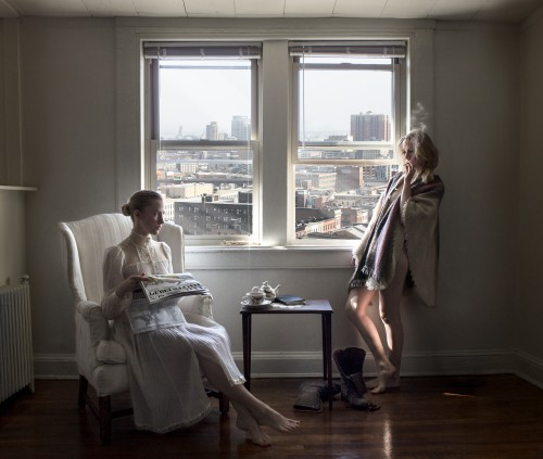 Photograph of two women in a room with a city view. One woman sits in a high backed chair wearing a victorian costume. The other stands smoking near the window draped in a blanket.