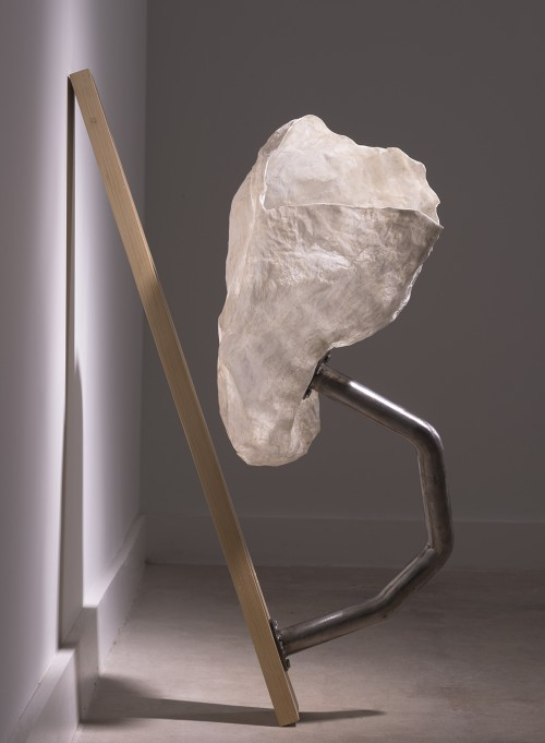 Delicate paper cup-like sculpture connected to a plank by a length of bent mental piping.