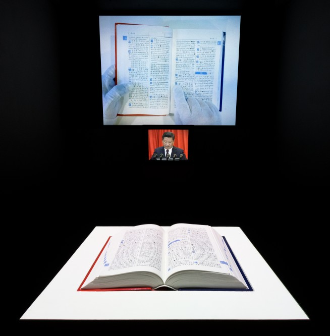 In the foreground, the Chinese dictionary on a pedestal. In the background, two projected videos. The larger video still is of a hand moving across the pages of a dictionary. The smaller still is of President Xi.