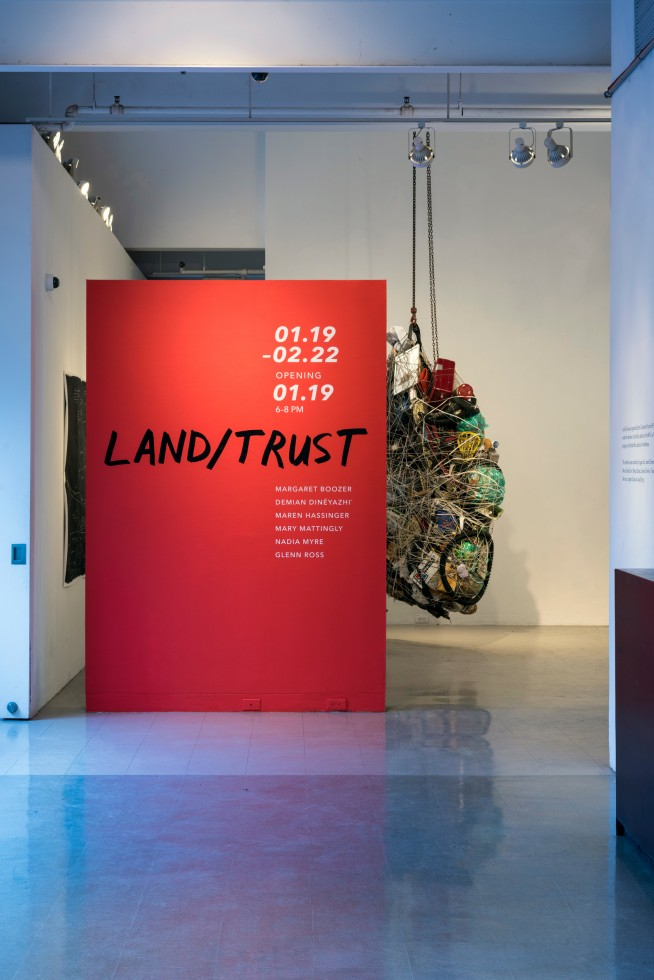 "Exhibition wall labeled ""LAND/TRUST"" with a large hanging piece of art in the background."