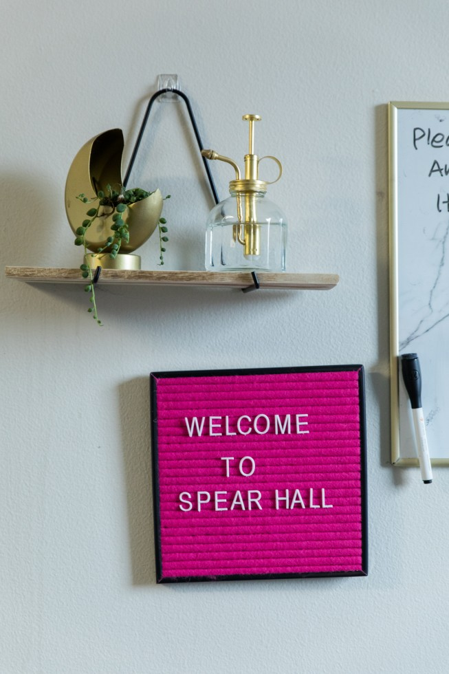 "Detail from a Spear Hall apartment. A felt board hangs on the wall with lettering that says ""welcome to Spear Hall."""