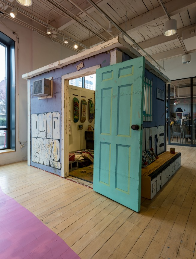 Cardboard structure painted like a shed. The shed is filled with items from skateboarding subculture, all also made of painted cardboard.