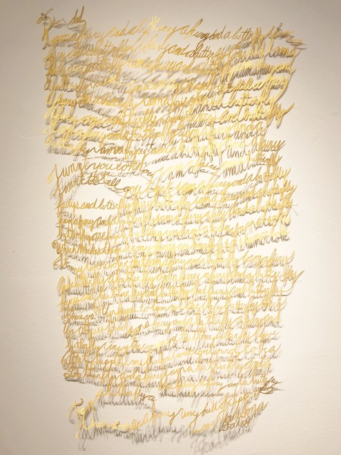 Handwritten script cut out of gold paper and hung against a white gallery wall.