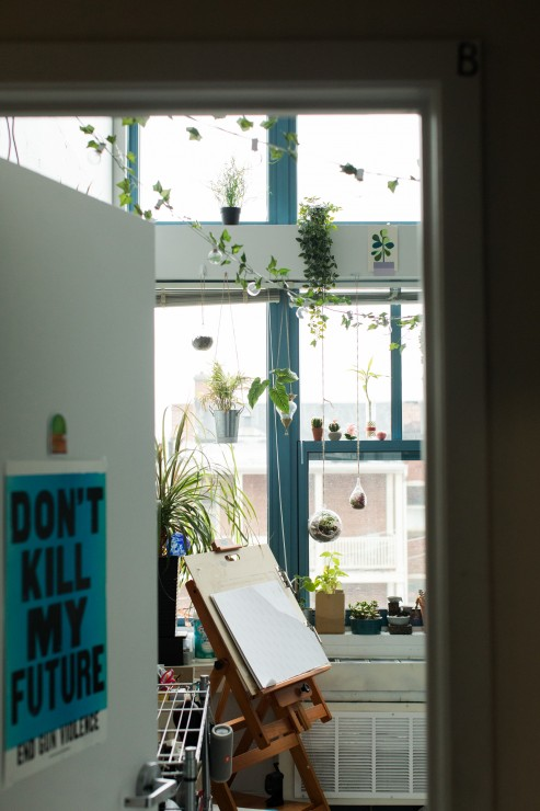 "Spear Hall apartment. Plants hang in the window and a sign on the bedroom door reads ""don't kill my future."""
