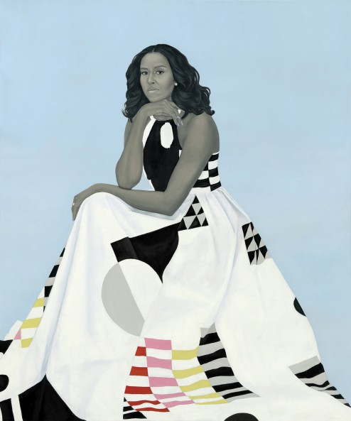 Portrait of Michelle Obama against a light blue background. She is sitting with her chin propped on the back of her hand and is wearing a black and white dress with geometric patters. Her skin and hair are all painted in shades of black and grey.