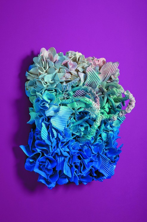 Rectangular stoneware of shells floral decoration and textured shells, glazed and acrylic stained with blue, sea foam green and pink gradient, hung on a purple background.