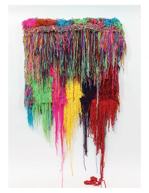 Multi-colored yarn cascades down a stretched canvas.
