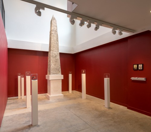Large carved obelisk in a gallery space that has been painted deep red. The obelisk is surrounded by intricately designed bronze gags and bridles encased in glass and set atop thin pedestals.